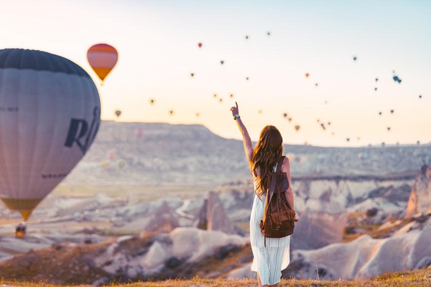 jeune femme en robe blanche au bout dun falaise qui pointe du doigt une montgolfiere dans le ciel