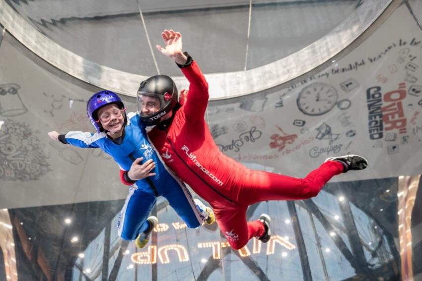 jeune femme qui effectue le simulateur de chute libre avec un accompagnateur