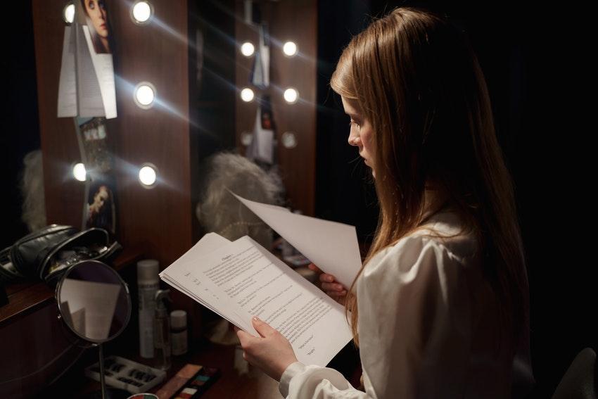 jeune femme qui lit son texte en loge dune salle de theatre
