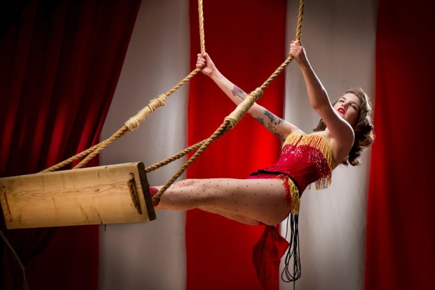 jeune femme trapeziste qui se balance dans un cirque