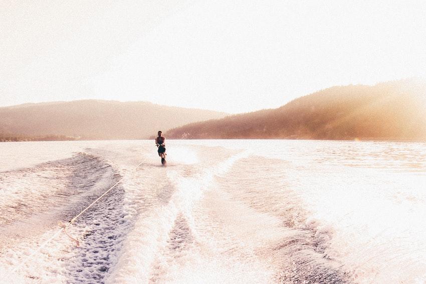 jeune homme sur un wakeboard au coucher du soleil