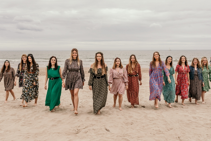 jeunes femmes sur la plage en robes a fleurs qui marchent en ligne dans le sable