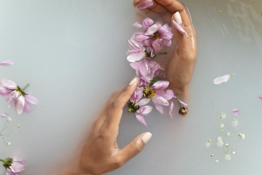 main dans leau avec petales de fleurs