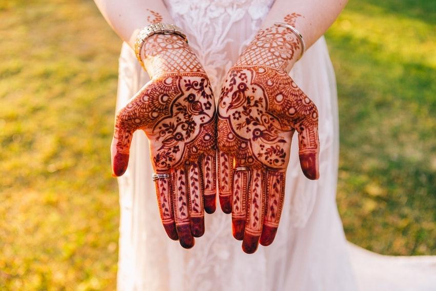 mains tatouees au henne femme avec robe blanche