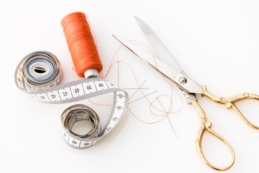 materiel de couture avec paire de ciseaux et fil rouge