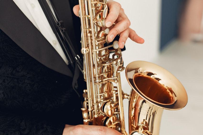 musicien en smoking qui joue du saxophone