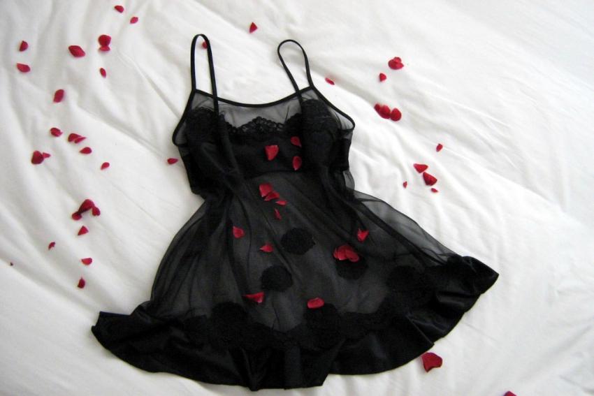 nuisette noire en dentelle sur un lit avec des petales de roses