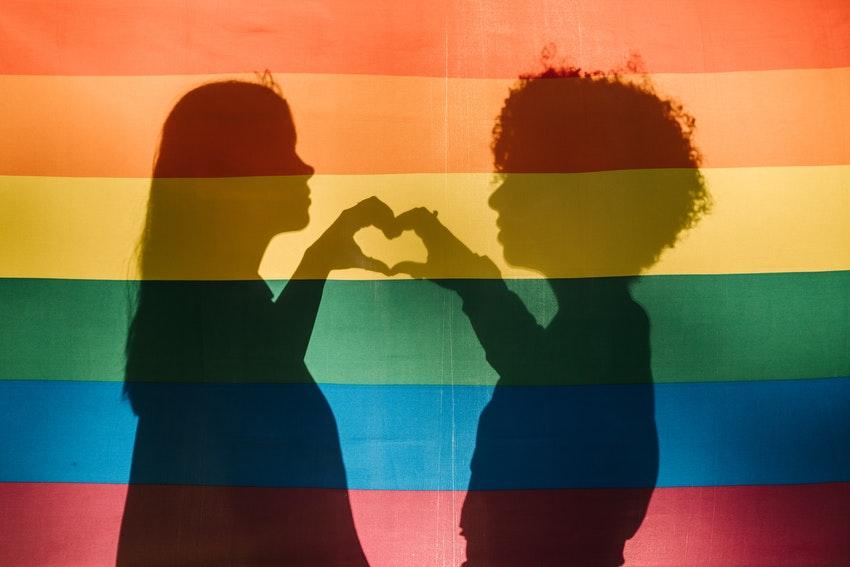 ombre de deux jeunes femmes sur le drapeau lgbt qui forme un coeur avec leurs mains