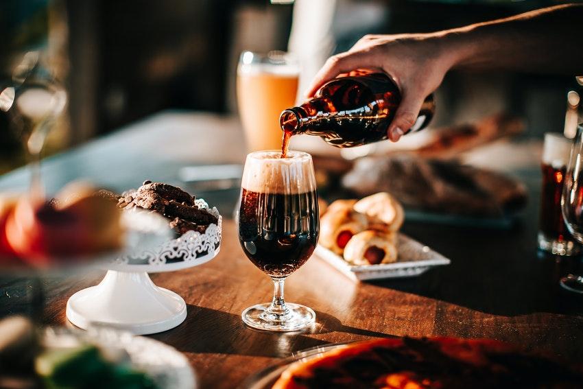 personne qui verse de la biere dans un verre sur une table avec repas