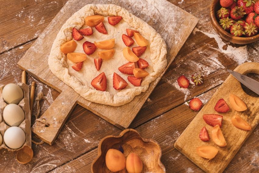 plan de travail avec tarte dans un plat a gateau avec fraise et abricot a linterieur