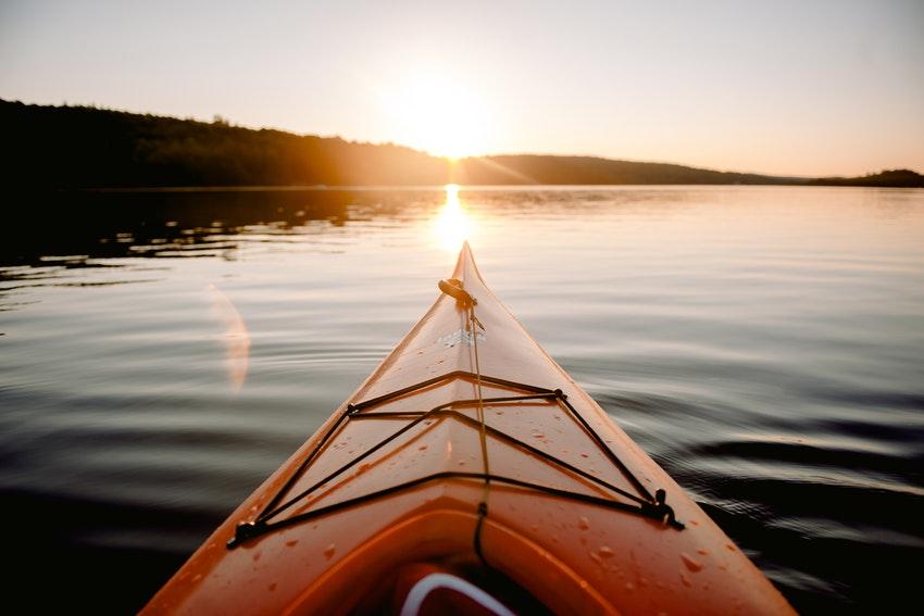 pointe dun kayak sur leau avec au loin la foret et le coucher du soleil