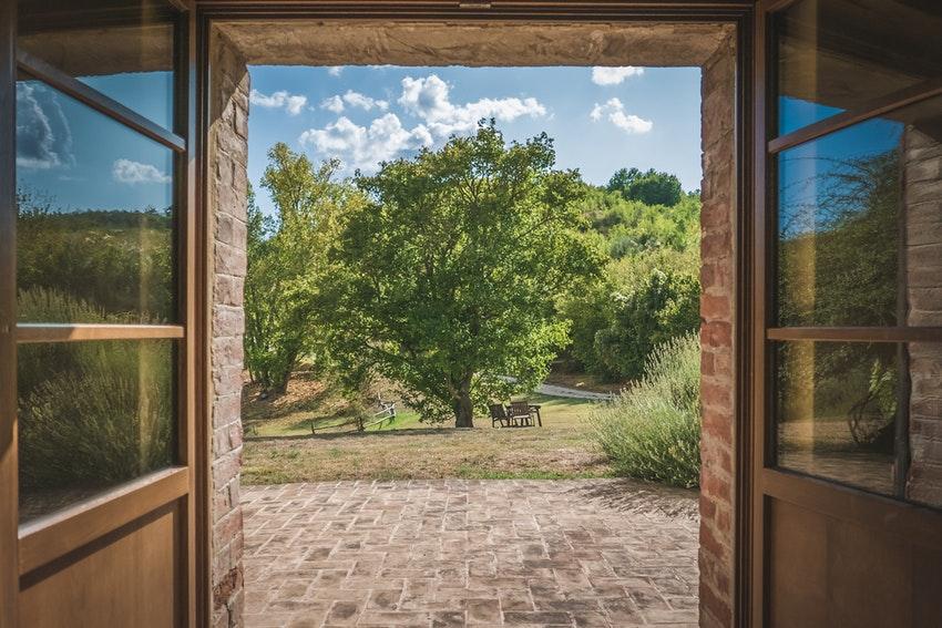 porte ouverte sur jardin avec arbre et chaise