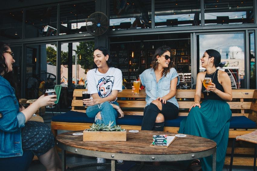quatre filles assisent a un table dans un bar entrain de rigoler et boire un verre