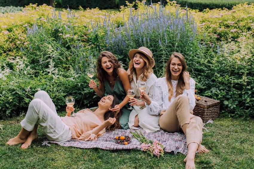 quatre filles assisent sur une nappe dans lherbe entrain de pique niquer