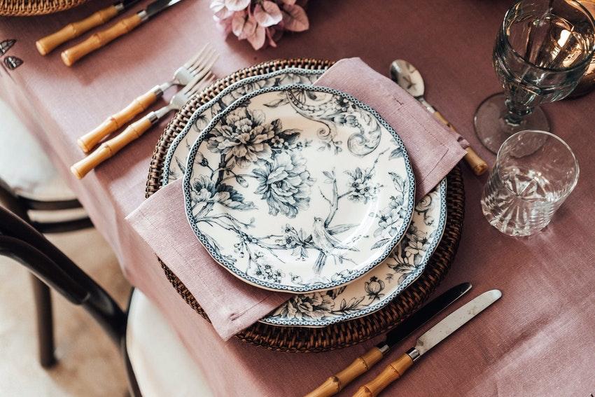 table avec nappe rose vaisselle en porcelaine et couverts en bambou
