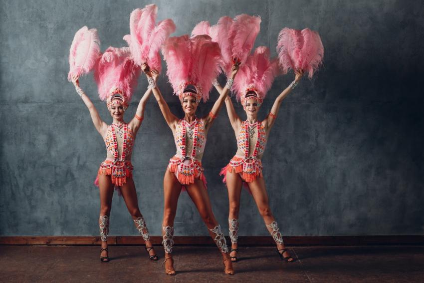 trois danseuses de cabaret en tenue et plumes