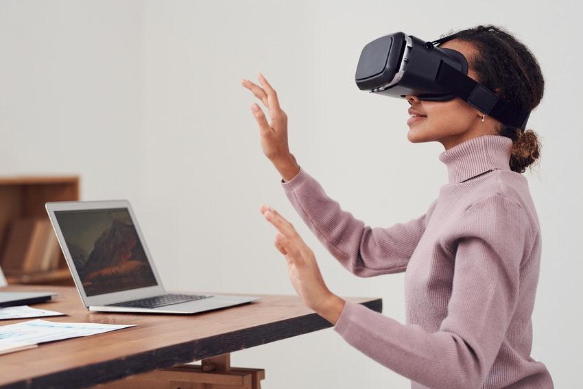 jeune femme assise devant son ordinateur qui essaye des lunettes de realite virutelle