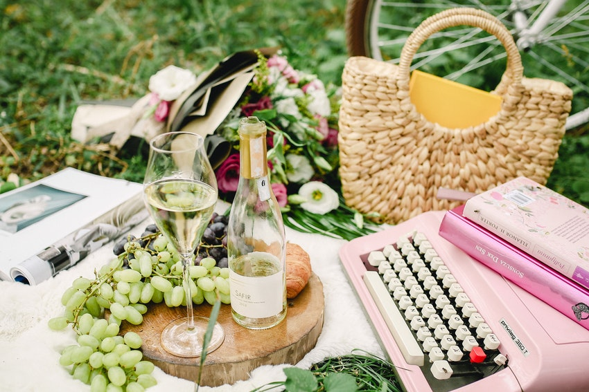 bouquet de fleurs bouteille de vin blanc machine a ecririe panier en osier et grappe de raisin