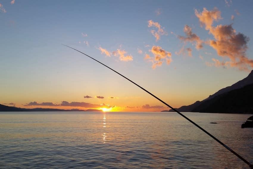 canne a peche devant la mer au coucher de soleil