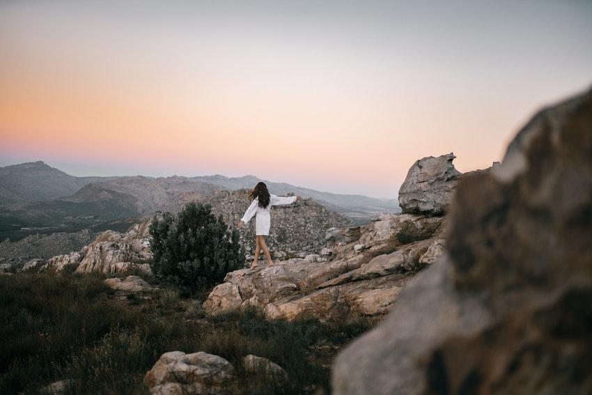 femme en robe blanche qui marche sur des rochers au coucher du soleil
