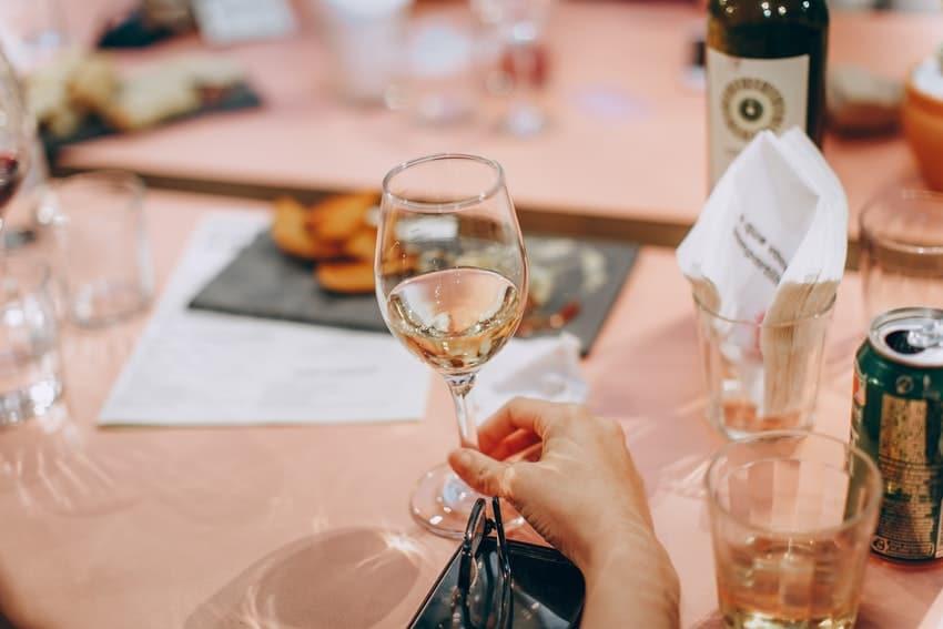 femme qui tient un verre de vin blanc a la main par le pied