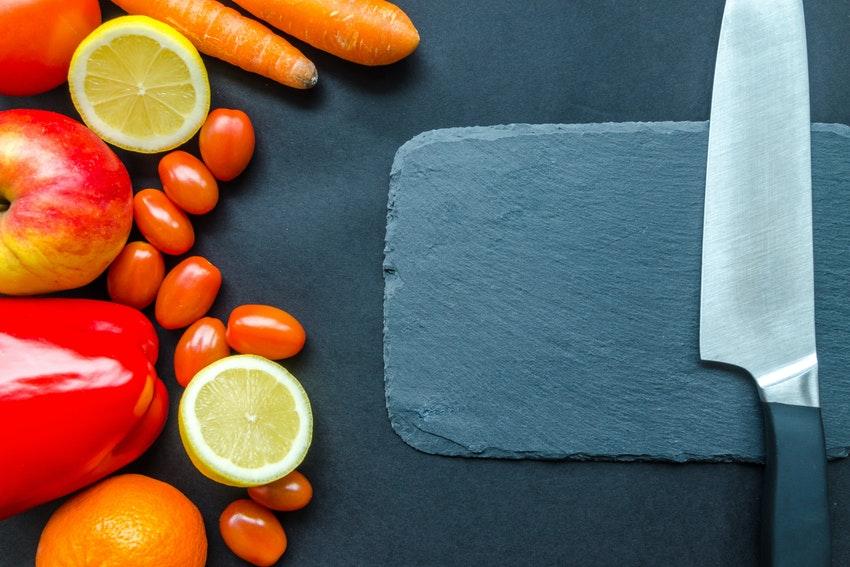 fruits et legumes sur un plan de travail avec planche a decouper et couteau de cuisine