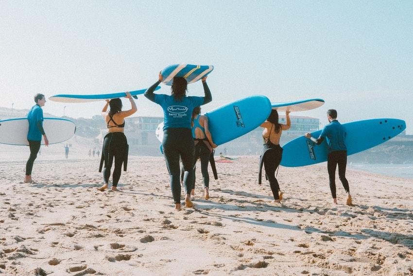 groupe de personnes en combianaison avec planches de surf bleues sur la plage