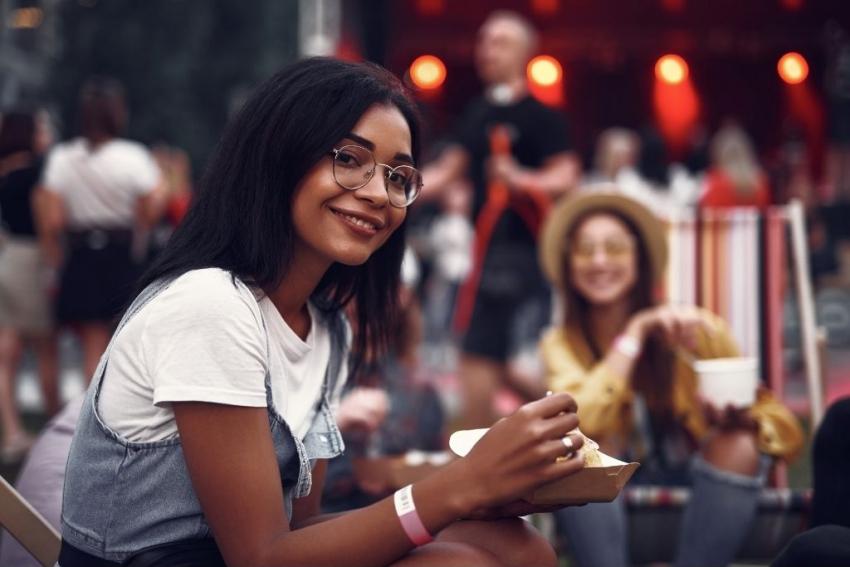 jeune femme assise devant une scene de concert entrain de manger