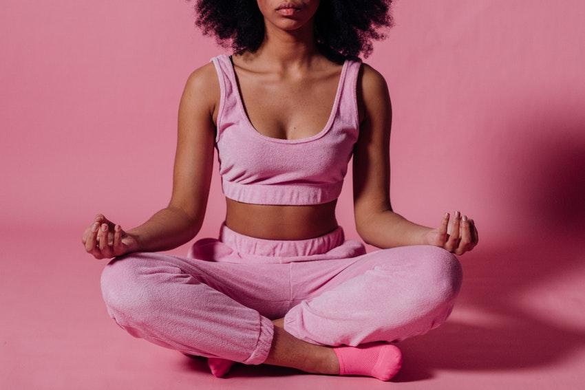 jeune femme habille en tenue de sport rose qui fait du yoga