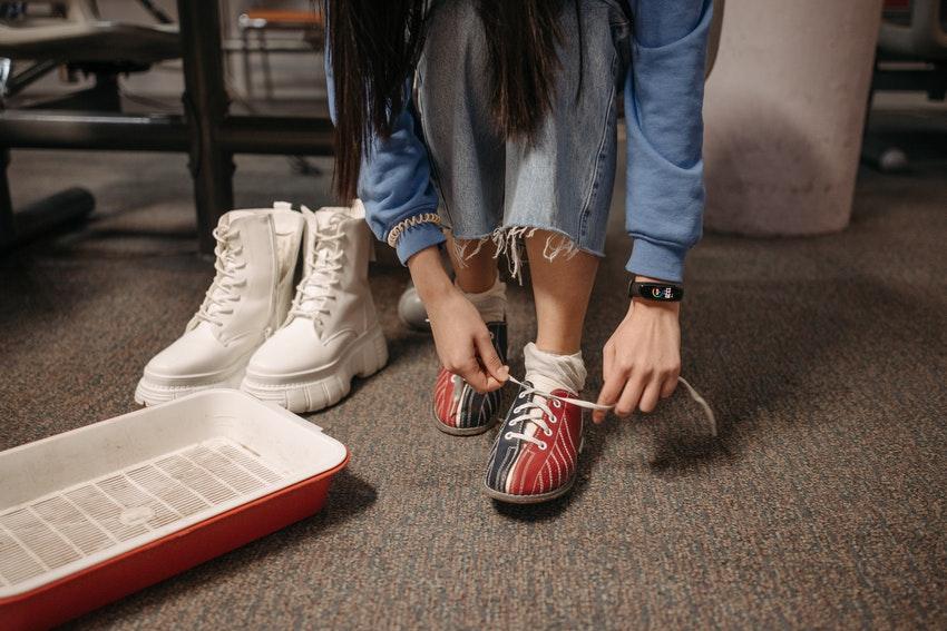 jeune fille entrain de lacer ses chaussures de bowling