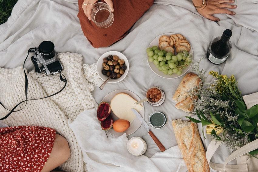 nappe blanche pique nique appareil photo bouquet de fleurs et bouteille de vin