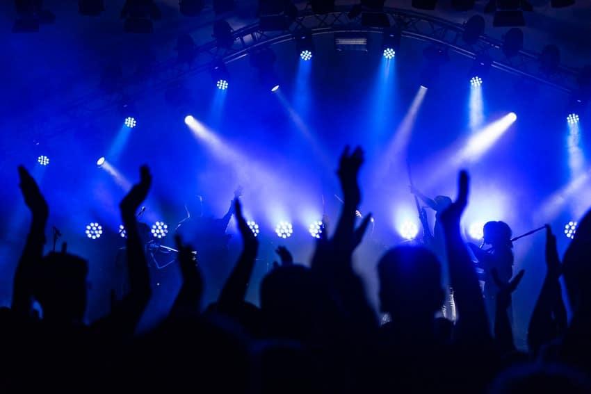 personnes qui danse devant scene de concert lumiere bleu