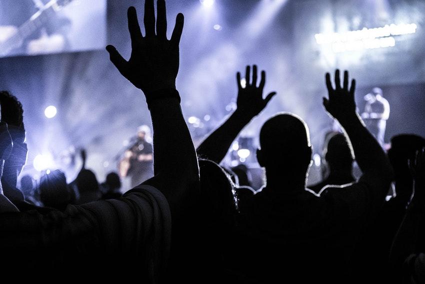 personnes qui dansent devant une scene de concert