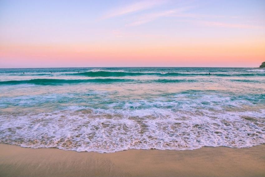 plage de sable et eau turquoise au coucher du soleil ciel rose