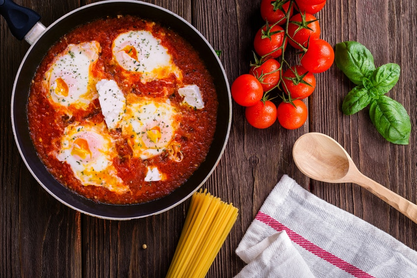 plat cuisine sur plan de travail avec tomates et ustzsiles de cuisine