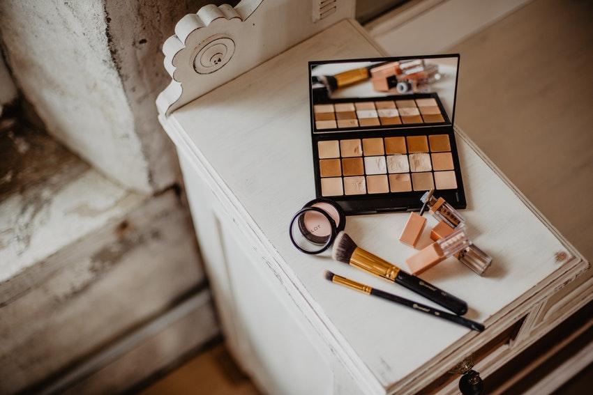 produits de maquillage poses sur un petit meuble blanc